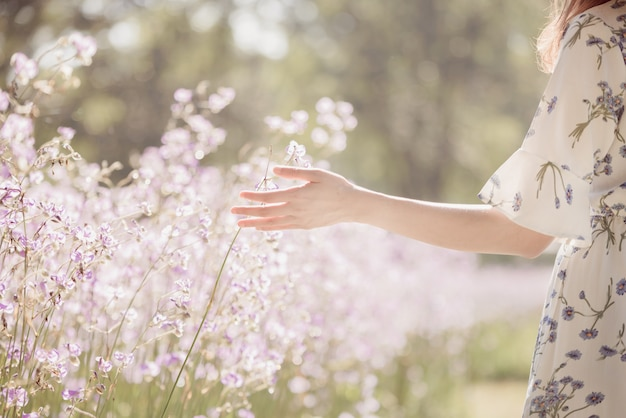 Fille avec son dos et chapeau de paille dans un champ de fleurs, heureuse femme asiatique