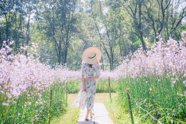 Fille avec son dos et son chapeau de paille dans un champ de fleurs