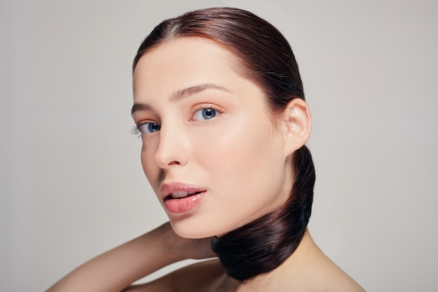 Une fille sophistiquée élégante aux lèvres charnues à la peau propre et délicate, tenant ses cheveux bruns à la main sur le gris. levage. soin du corps.