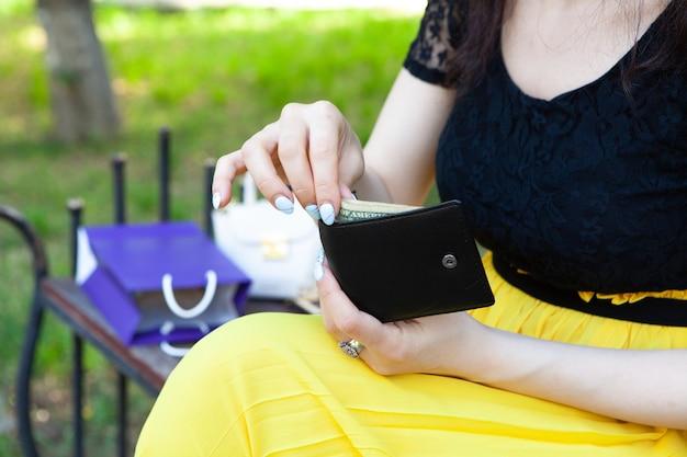 Une fille sort de l'argent du portefeuille dans le parc