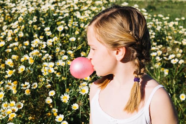 Fille soufflant bubble-gum dans le champ de camomille