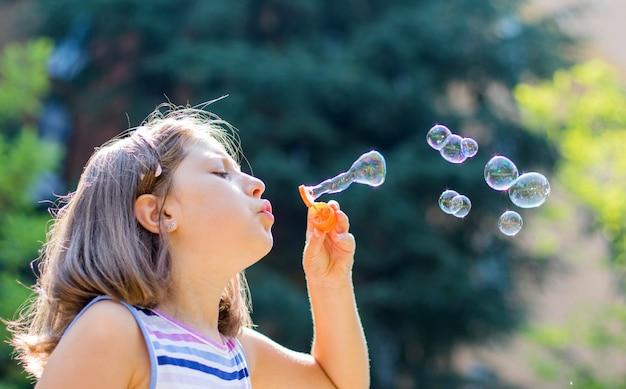 Fille soufflant des bulles de savon dans le parc dans une journée ensoleillée