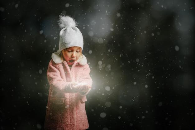 Fille soufflant dans la neige sur