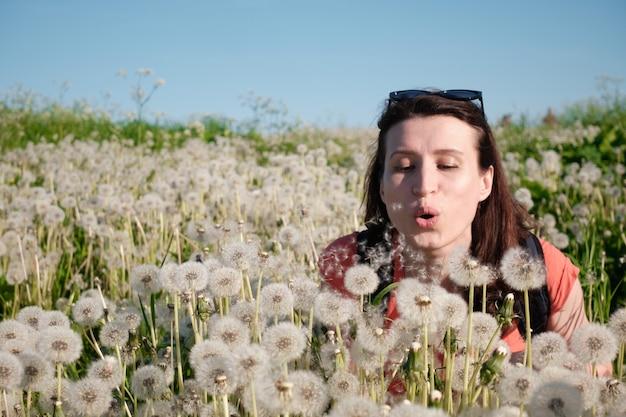 La fille souffle les graines des pissenlits.