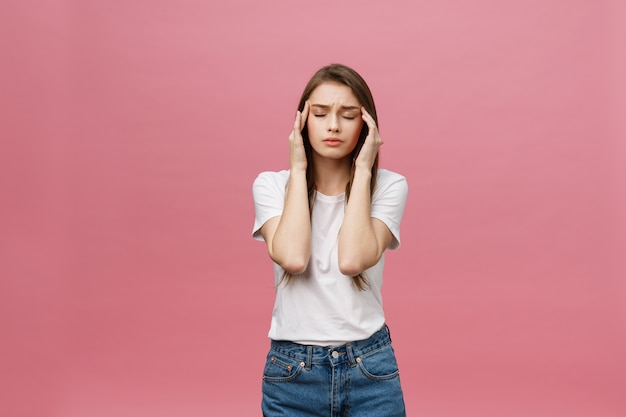 La fille souffre de terribles maux de tête et comprime la tête avec les doigts