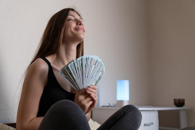 Une fille soulagée et heureuse devient riche après avoir fait beaucoup, se serrant la main