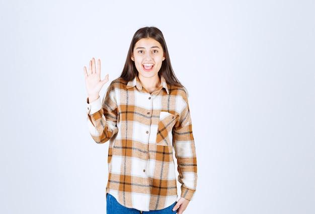 Fille souriante agitant une main sur un mur blanc-gris.