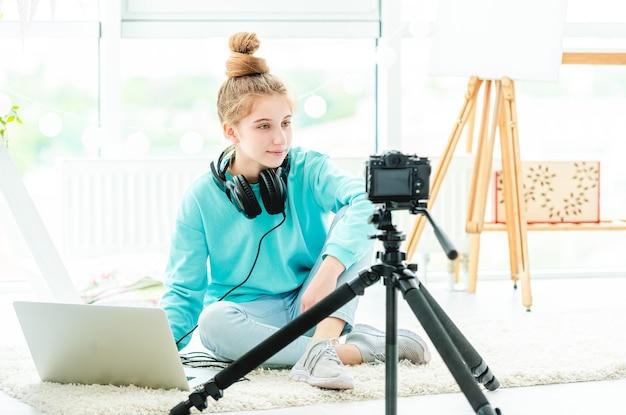 Fille souriante à l'aide d'un ordinateur portable et d'un appareil photo
