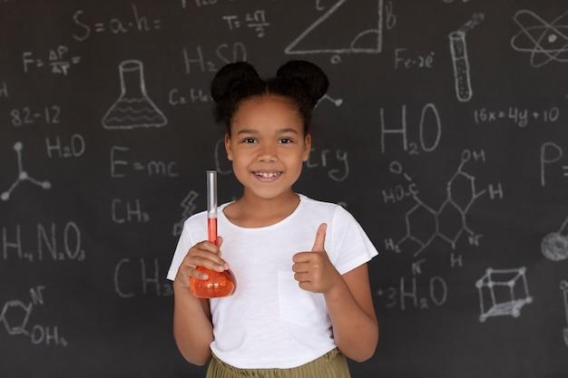 Fille souriante en apprenant plus sur la chimie en classe
