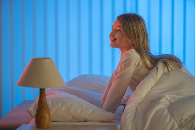 La fille souriante assise sur le lit. le soir la nuit