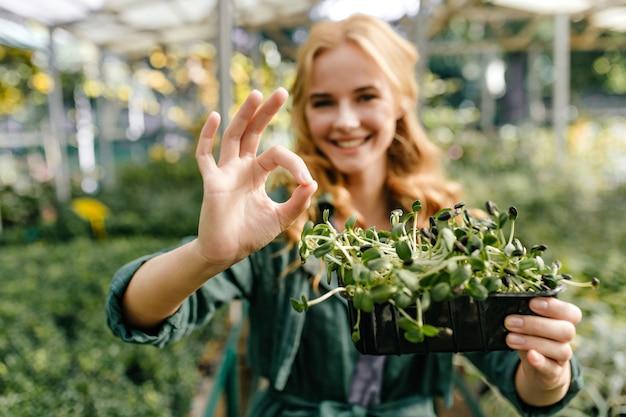 Une fille souriante aux cheveux roux sourit doucement et montre qu'elle va bien.