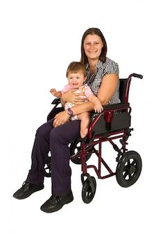 Une fille souriante avec un bébé dans un fauteuil roulant isolé sur blanc