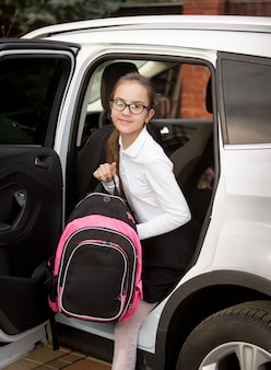 Fille souriante avec cartable sortant de la voiture