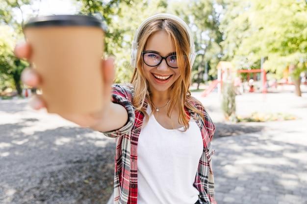 Fille souriante confiante posant dans le parc. joyeuse femme blonde tenant une tasse de café sur la nature.