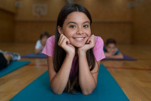 Fille souriante de coup moyen sur un tapis de yoga