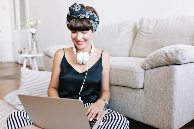 Fille souriante en débardeur en soie noire travaillant avec un ordinateur portable dans sa chambre confortable et lumineuse