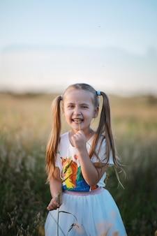 Une fille souriante avec deux queues sur la tête vêtue d'un short avec une licorne se promène dans un champ