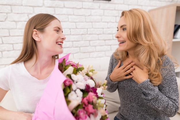 Fille souriante donne à la mère des fleurs et des cadeaux.
