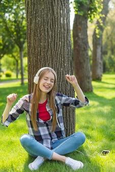 Fille souriante, écouter de la musique assis sur l'herbe