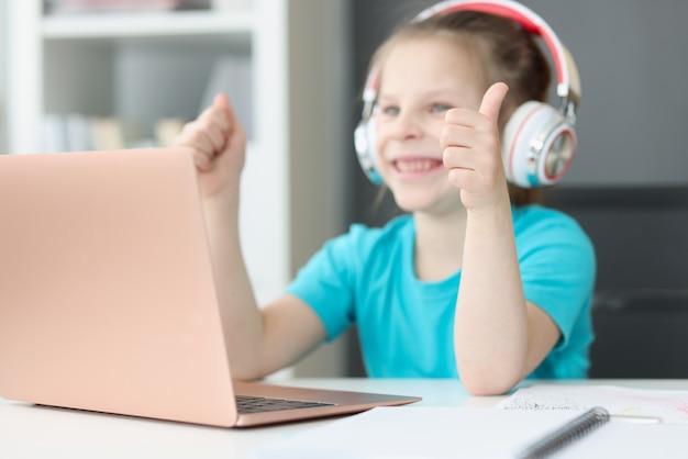 Une fille souriante est assise devant un ordinateur portable dans les écouteurs et montre son pouce