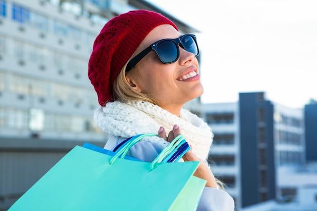 Fille souriante faisant ses courses avec des lunettes de soleil