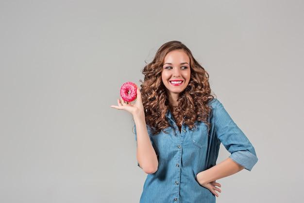 La fille souriante avec un gâteau rond sur un mur gris. cheveux longs.