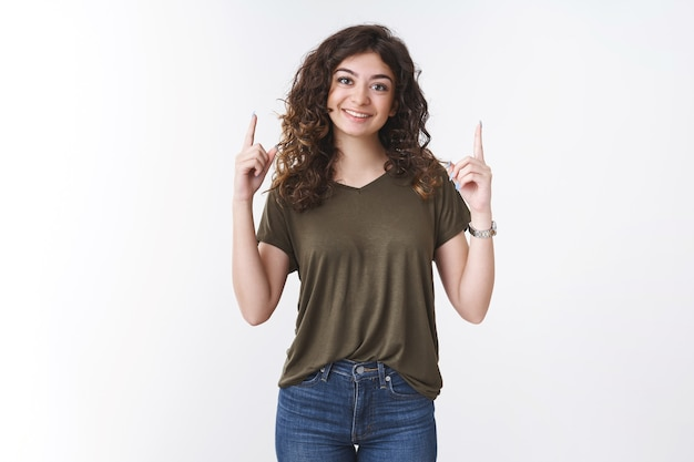 Fille souriante heureuse énergisée, dents parfaites, coiffure bouclée, lève l'index pointant vers le haut, suggérant d'essayer d'utiliser le produit, service de recommandation de publicité, fond blanc debout