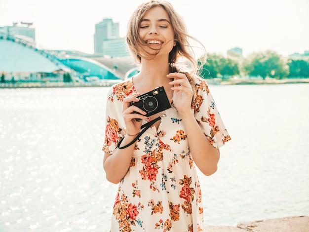Fille souriante hipster en robe d'été à la mode tenant une caméra rétro