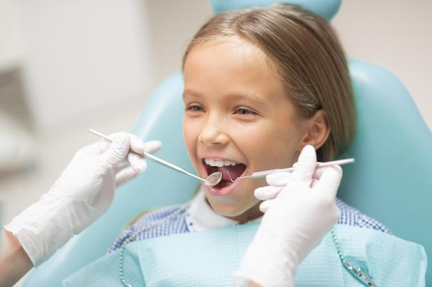 Fille souriante. jolie fille séduisante aux cheveux noirs souriante lors d'une visite chez le dentiste le week-end