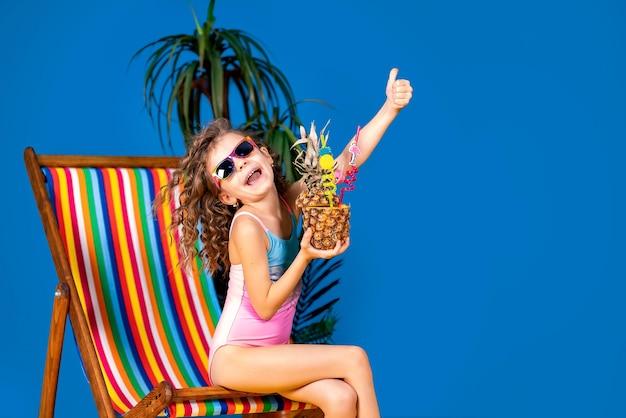 Fille souriante en maillot de bain et lunettes de soleil assis dans le pont arc-en-ciel