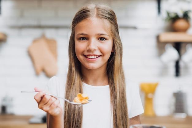 Fille souriante mangeant ses céréales