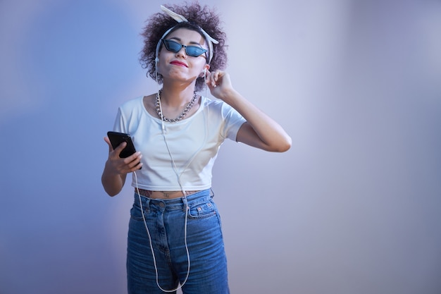 Une fille souriante à la mode avec des boucles afro écoute et apprécie la musique avec des écouteurs, un modèle de style hip hop avec un smartphone se détendre