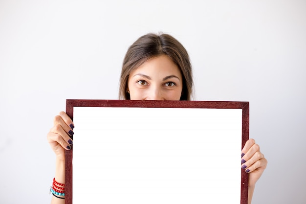 Fille souriante montrant une pancarte blanche vierge ou une affiche