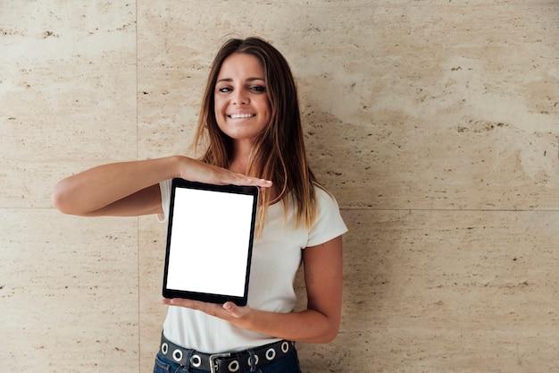 Fille souriante montrant une tablette avec maquette