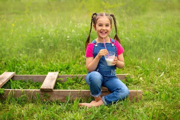 Fille souriante avec des nattes en salopette en denim et un t-shirt rose, tient un verre de lait avec une paille rose