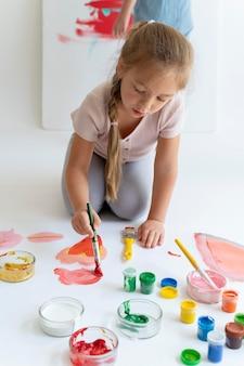 Fille souriante peignant avec un pinceau plein coup