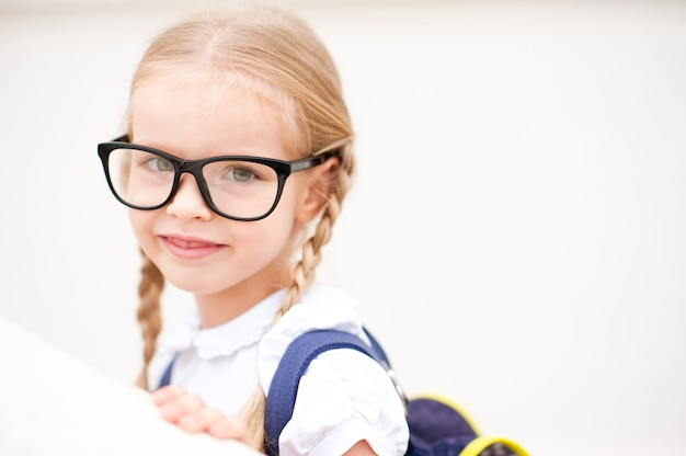 Fille souriante portant des lunettes et un sac d'école à l'extérieur