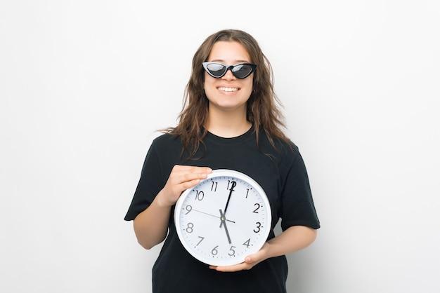 Une fille souriante portant des lunettes de soleil tient une grosse horloge murale ronde.