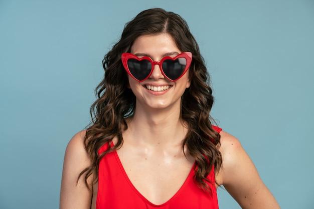 Fille souriante et positive dans des lunettes de soleil en forme de coeur