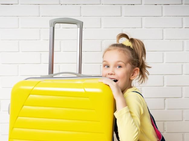 Une fille souriante avec une queue de cheval en pull en jean tient une valise jaune sur fond de briques blanches