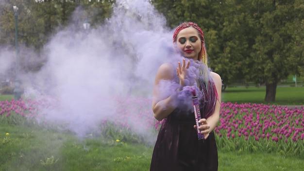 Fille souriante en robe de satin violet avec de longues tresses multicolores et un maquillage scintillant accrocheur. la fumée de couleur pourpre couvre la fille dans le parc printanier