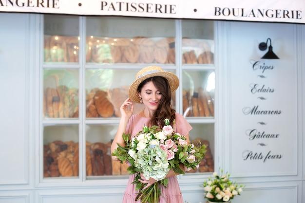 Une fille souriante se tient près de la boulangerie de la fenêtre en chapeau de paille avec un bouquet de fleurs cadeau surprise