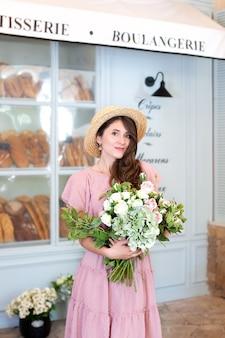 Fille souriante se tient près de la boulangerie de la fenêtre en chapeau de paille avec un bouquet de fleurs cadeau