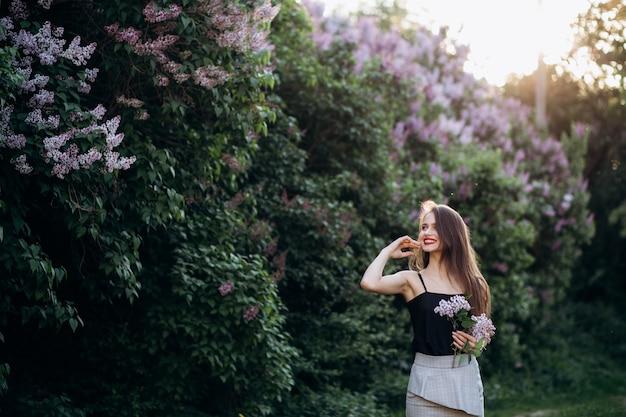 La fille souriante se tient près des buissons avec des fleurs
