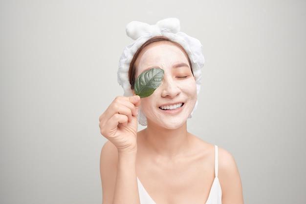 Une Fille Souriante Avec Une Serviette Rose Sur La Tête A Appliqué Un Masque Hydratant à L'argile Tout En Tenant Une Feuille Photo Premium