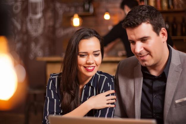 Fille souriante et son partenaire commercial ayant un appel vidéo dans un café. entreprise moderne. bonne concentration.