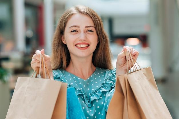 Fille souriante tenant des sacs à provisions