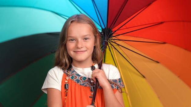 Fille souriante tient un parapluie multicolore lumineux ouvert. enfant caucasien regarde et sourit.