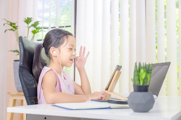 Fille souriante et tout en utilisant un ordinateur portable et des écouteurs sans fil pour appel vidéo