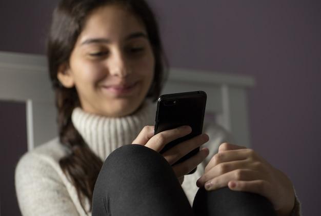 Fille souriante tout en utilisant un smartphone à l'intérieur